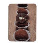 Row of chocolate truffles on wood magnet