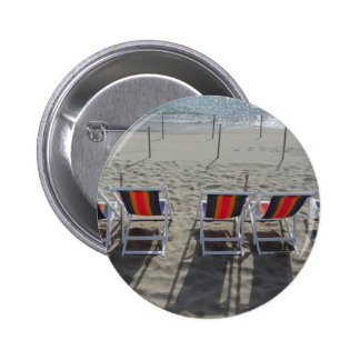 Row of colorful wooden chairs at beach button