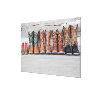 Row of cowboy boot on porch of log cabin canvas print