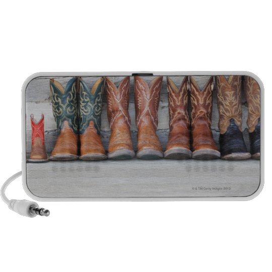 Row of cowboy boot on porch of log cabin speaker