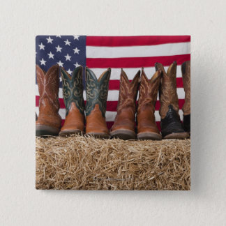Row of cowboy boots on haystack button