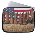 Row of cowboy boots on haystack computer sleeves