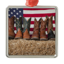 Row of cowboy boots on haystack metal ornament