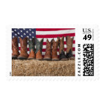 Row of cowboy boots on haystack postage