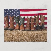 Row of cowboy boots on haystack postcard