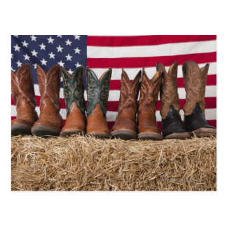 Row of cowboy boots on haystack postcard