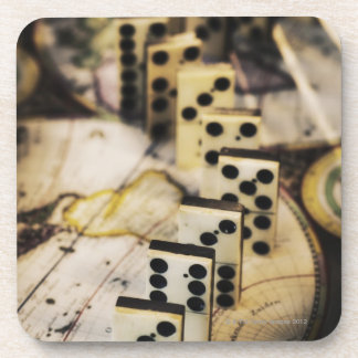 Row of dominoes on old world map coaster