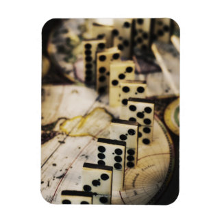 Row of dominoes on old world map magnet