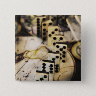 Row of dominoes on old world map pinback button