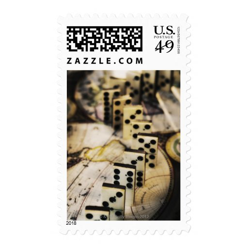 Row of dominoes on old world map postage stamps
