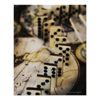 Row of dominoes on old world map poster
