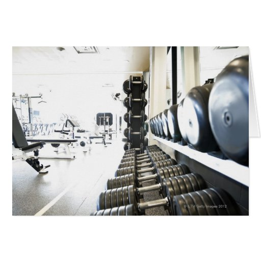 Row of free weights in foreground and exercise greeting card