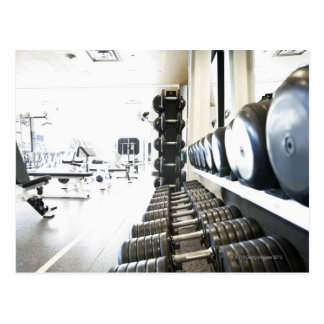Row of free weights in foreground and exercise postcard