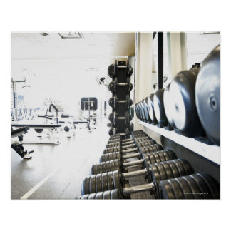 Row of free weights in foreground and exercise poster