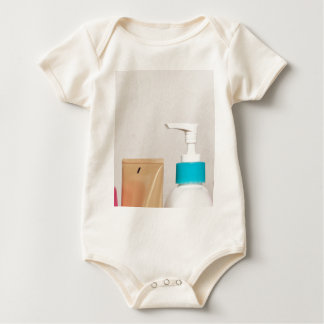 Row of toiletry bottles baby bodysuit