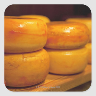 rows of colourful yellow Edam cheeses lined up Square Sticker