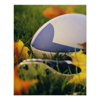 Rugby ball and shoe on lawn in autumn posters