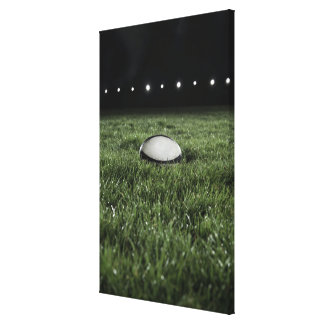 Rugby ball sitting on the grass pitch of a stretched canvas print