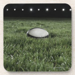 Rugby ball sitting on the grass pitch of a drink coaster