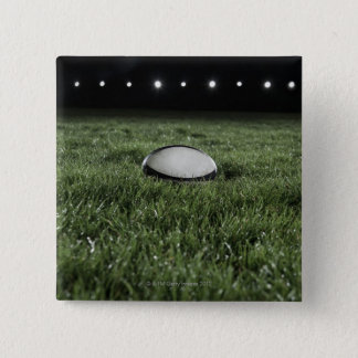 Rugby ball sitting on the grass pitch of a pinback button