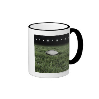 Rugby ball sitting on the grass pitch of a ringer coffee mug