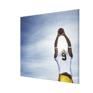 rugby player holding ball up with body stretched canvas print