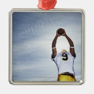 rugby player holding ball up with body stretched ornaments