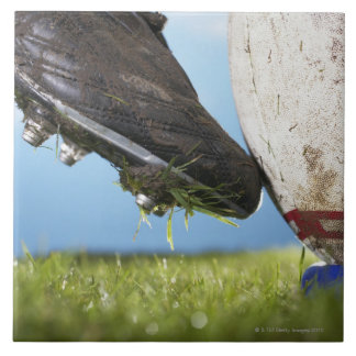 Rugby player kicking ball off tee, close up of tile