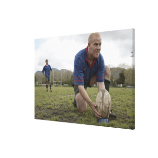 Rugby player positioning ball on rugby pitch canvas print