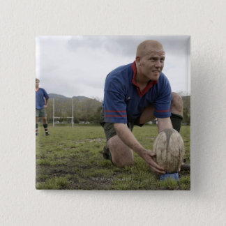 Rugby player positioning ball on rugby pitch pinback button