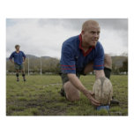 Rugby player positioning ball on rugby pitch poster