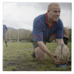 Rugby player positioning ball on rugby pitch tiles