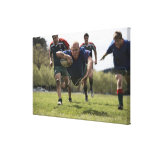 Rugby player scoring jumping on groud with ball canvas prints