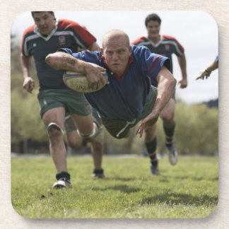 Rugby player scoring jumping on groud with ball drink coaster