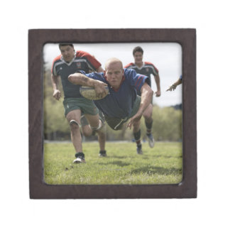 Rugby player scoring jumping on groud with ball gift box
