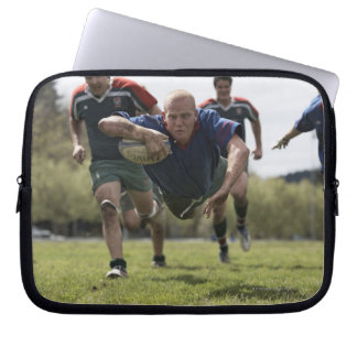Rugby player scoring jumping on groud with ball laptop sleeve