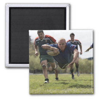 Rugby player scoring jumping on groud with ball magnet