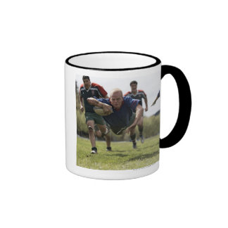 Rugby player scoring jumping on groud with ball mugs