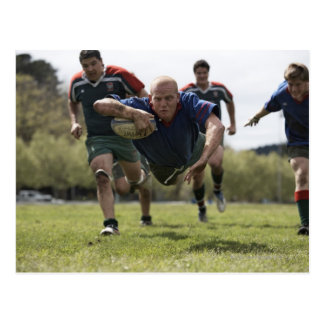 Rugby player scoring jumping on groud with ball postcard
