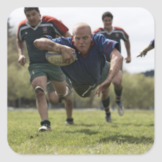 Rugby player scoring jumping on groud with ball square sticker