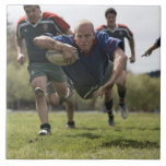 Rugby player scoring jumping on groud with ball tiles