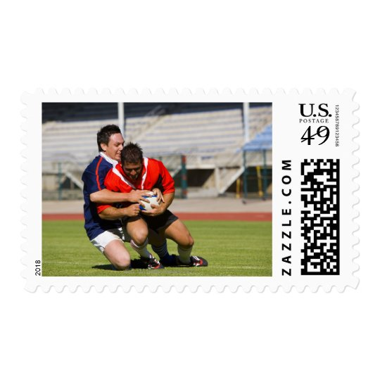 Rugby players fighting for ball postage