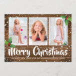 """Rustic Country Winter Merry Christmas Photo Holiday Card<br><div class=""""desc"""">Country style christmas holiday card featuring a rustic wood background,  a collage of 3 photos for you to personalize,  festive holly,  a snow shower,  the words """"merry christmas"""" in a calligraphy typeface and your seasons greetings underneath.</div>"""