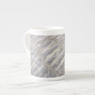Rustic heart in the sand, textured beach tea cup