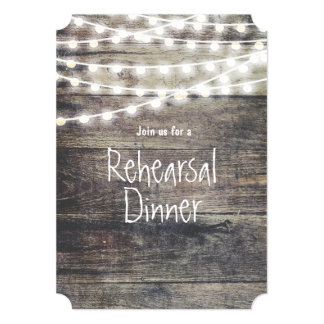 Rustic wood and string lights rehearsal dinner card