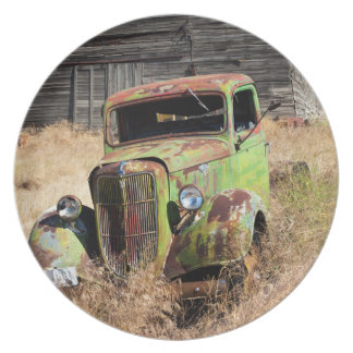 Rusting car in front of abandoned farm dinner plate