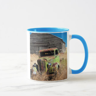 Rusting car in front of abandoned farm mug