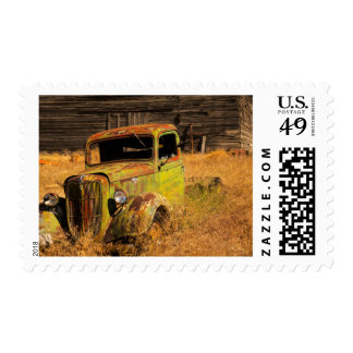 Rusting green truck in front of abandoned farm postage