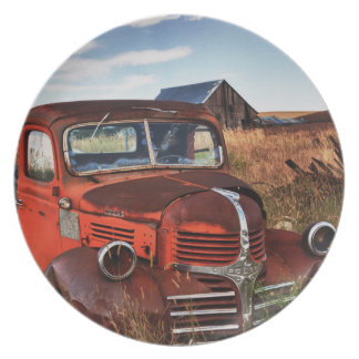 Rusting orange Dodge truck with abandoned farm Plate