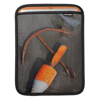 Rusty Anchor And Buoy On A Beach Sleeves For iPads
